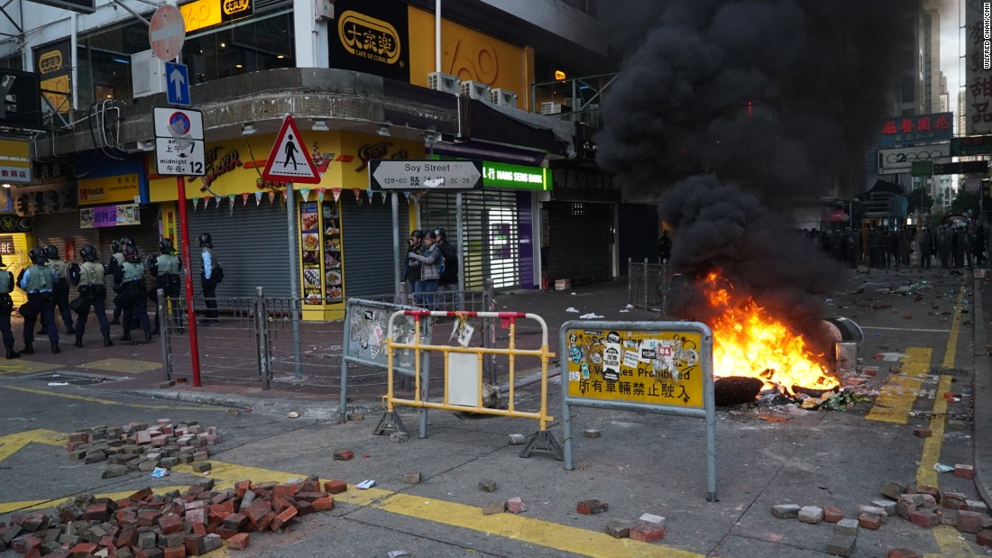 Objects are set on fire as bricks lay scattered about at an intersection in Mong Kok, a busy shopping district.