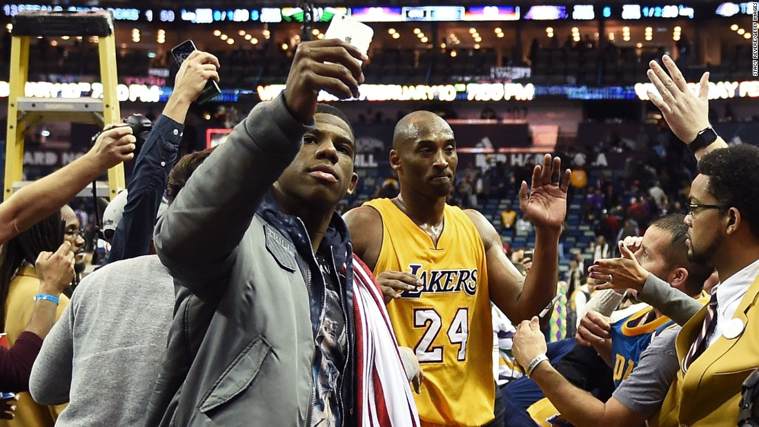 A fan snaps a photo with basketball star Kobe Bryant after an NBA game in New Orleans on Thursday, February 4.