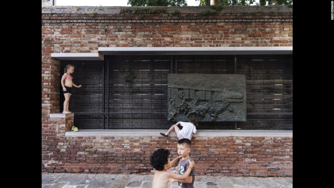 Children play in front of a memorial for Venetian Jews who were deported during World War II.