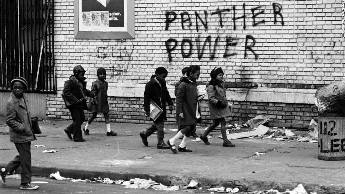 Children walk by Panther Power graffiti. The group saw themselves as the vanguard of a worldwide revolution, a revolution that had sparked uprisings in places like Vietnam and Cuba in the 1960s.