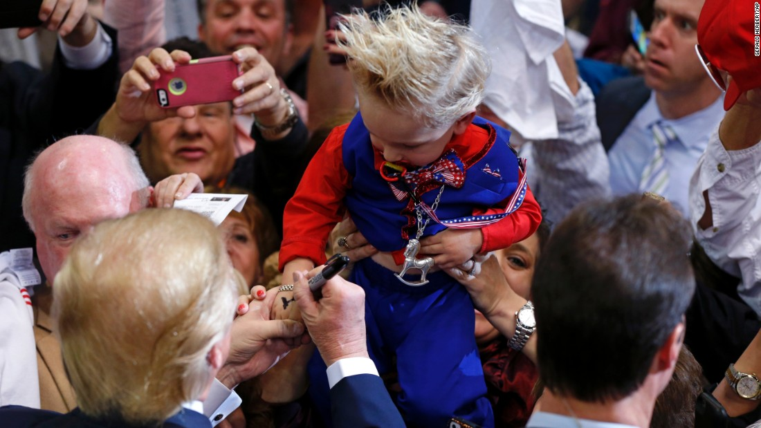 Republican presidential candidate Donald Trump signs the hand of Curtis Ray Jeffrey II at a campaign rally in Baton Rouge, Louisiana, on Thursday, February 11. The young boy's hair was styled to resemble Trump's.