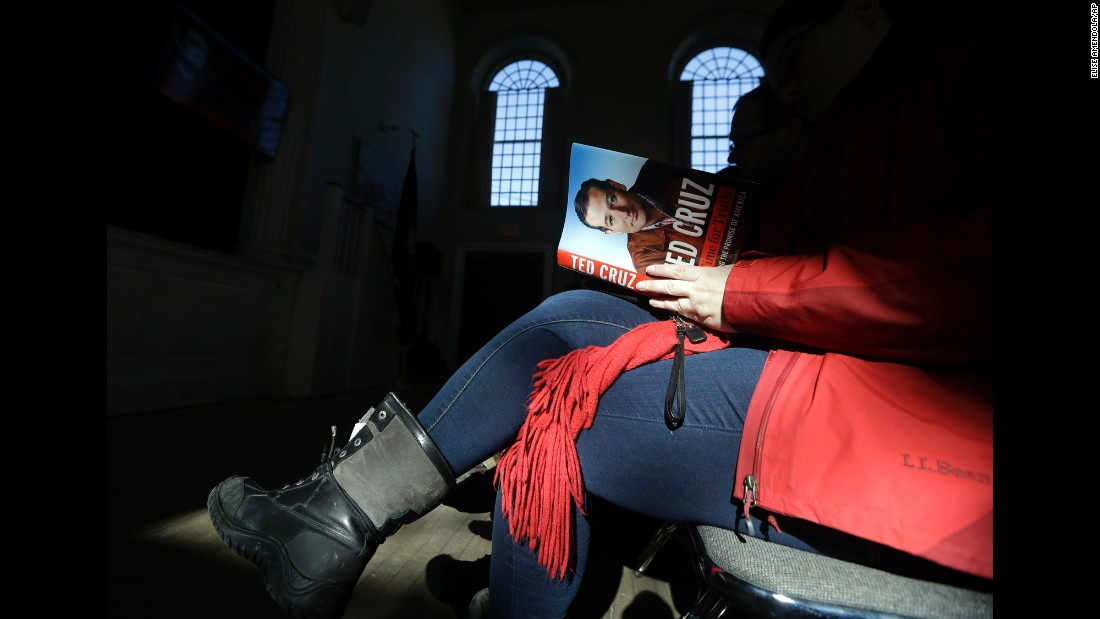 A woman reads a book by Sen. Ted Cruz before the Republican presidential candidate arrived for a campaign event in Peterborough, New Hampshire, on Sunday, February 7.