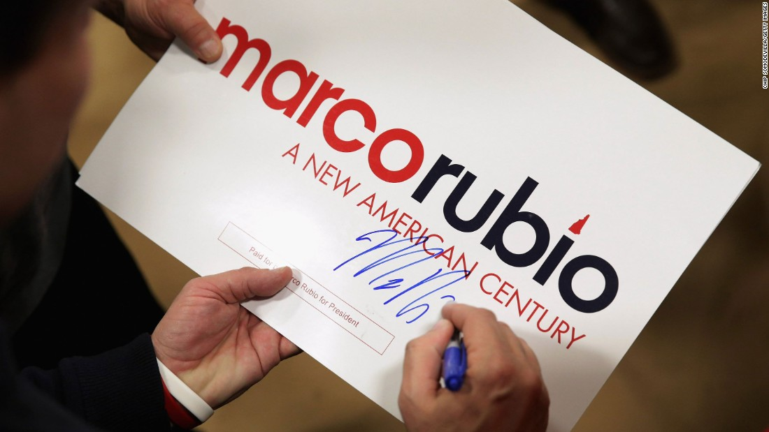 "Republican presidential candidate Sen. Marco Rubio signs autographs under his ""A New American Century"" slogan at a campaign rally February 5."
