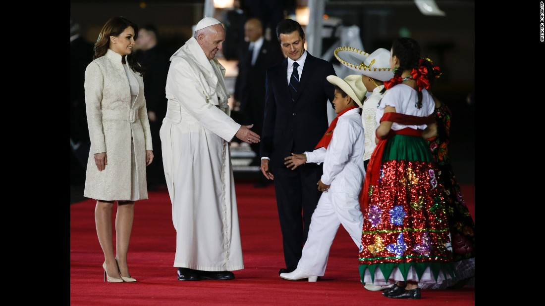 Pope Francis greets youth dressed in traditional outfits as he's escorted by Pena Nieto and first lady Angelica Rivera on Friday, February 12.