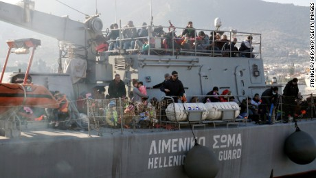 Migrants and refugees arrive aboard a Hellenic coast guard ship at the port of Lesbos island on February 8, 2016.  Streams of people fleeing conflict or poverty continue to make the often perilous journey from Turkey across the Mediterranean and through the Balkans, despite cold winter weather, in the hope of starting new lives in more prosperous European countries / AFP / STRINGER