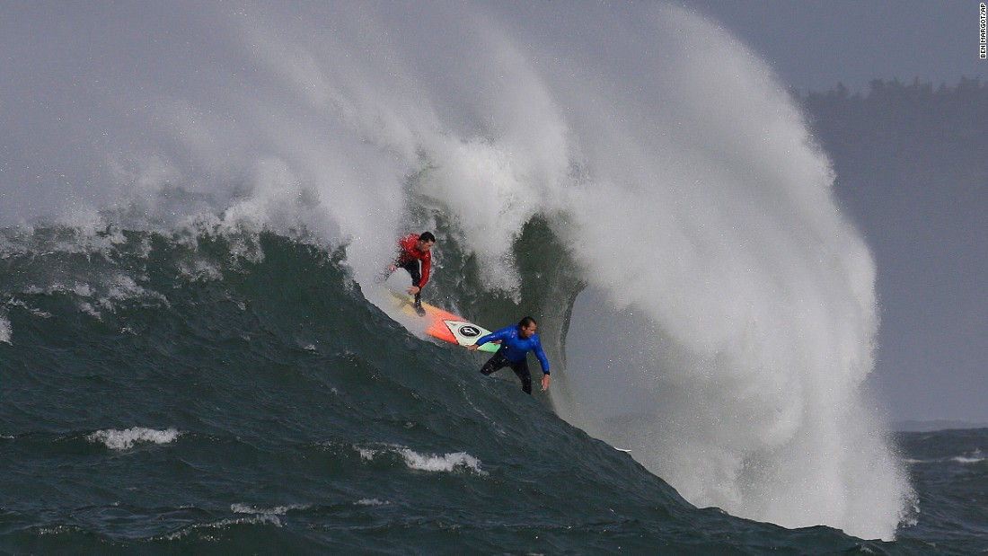 Ken Collins, left, and Chris Bertish surf a giant wave during the Mavericks surfing contest in Half Moon Bay, California, on Friday, February 12.