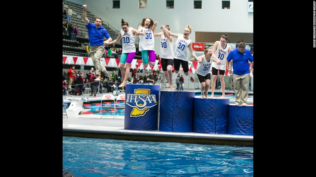 After winning their 30th straight state title -- a new national record in any sport -- swimmers from Indiana's Carmel High School jump into the water with their coaches on Saturday, February 13.