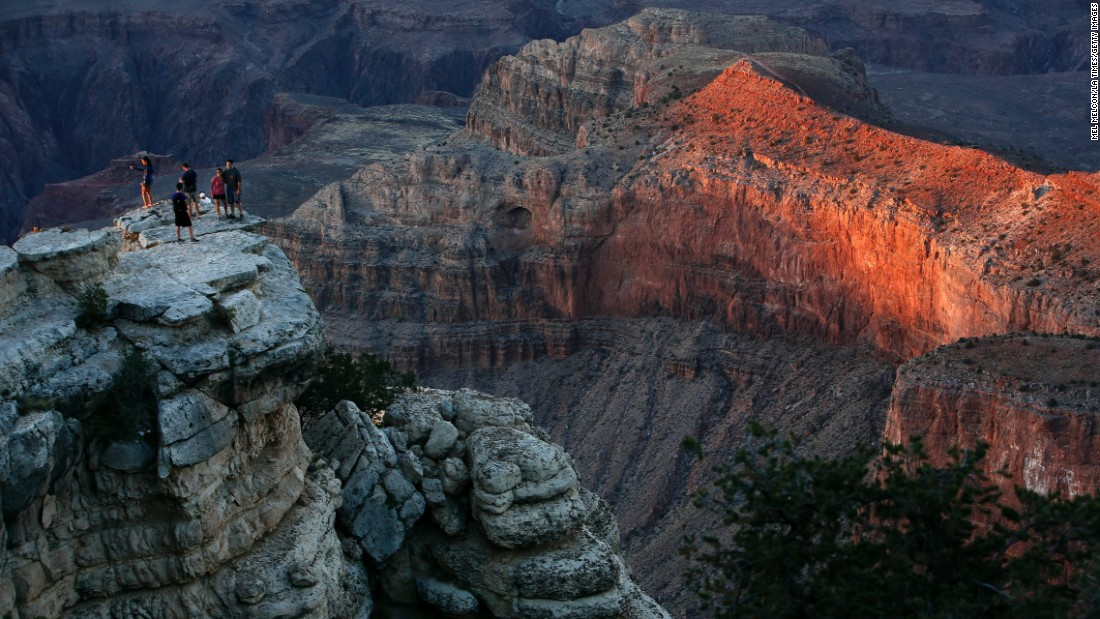 "Second place <a href=""http://www.cnn.com/2013/07/25/travel/grand-canyon-summer-park/"">Grand Canyon National Park</a> in Arizona welcomed more than 5 million visits last year, a record for the park. As the National Park Service marks its centennial birthday year, officials are expecting more visitors at many of the nation's park sites. Visitors are shown here at sunset on the Southern Rim of Grand Canyon National Park standing on a cliff off of the Rim Trail."