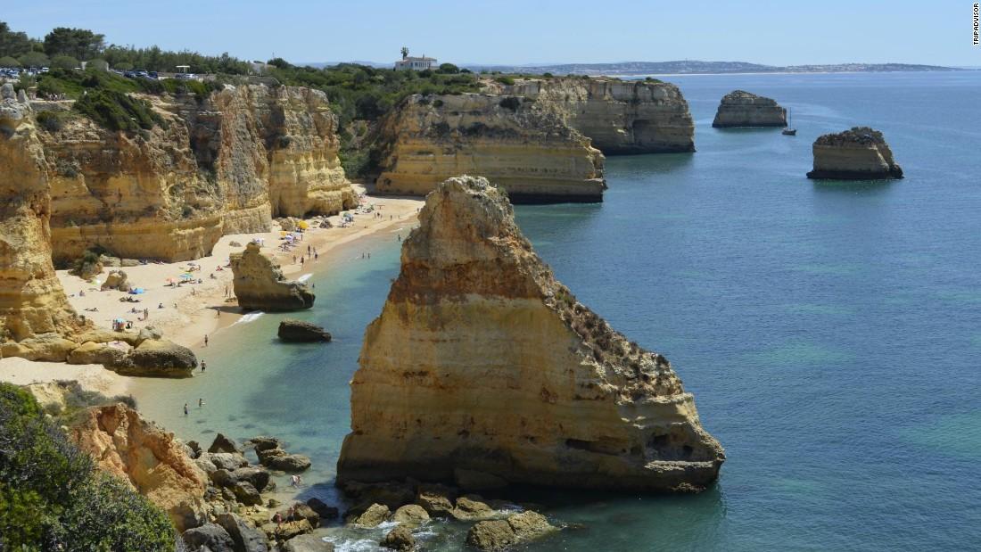 Stunning rock formations dot the shoreline at Praia da Marinha in Carvoeiro, Portugal.
