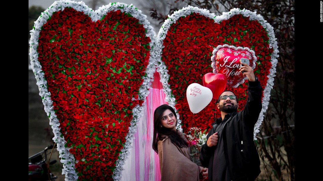 A couple takes a selfie in front of a heart-shaped bouquet display in Islamabad, Pakistan, on Valentine's Day.