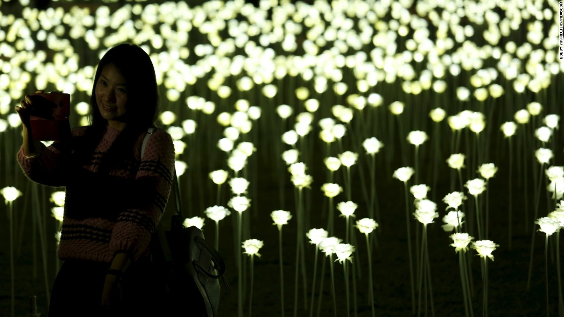 "A woman in Hong Kong takes a selfie in front of LED lights shaped like white roses on Saturday, February 13. <a href=""http://www.cnn.com/2016/02/10/living/gallery/look-at-me-selfies-0210/index.html"" target=""_blank"">See 20 selfies from last week</a>"