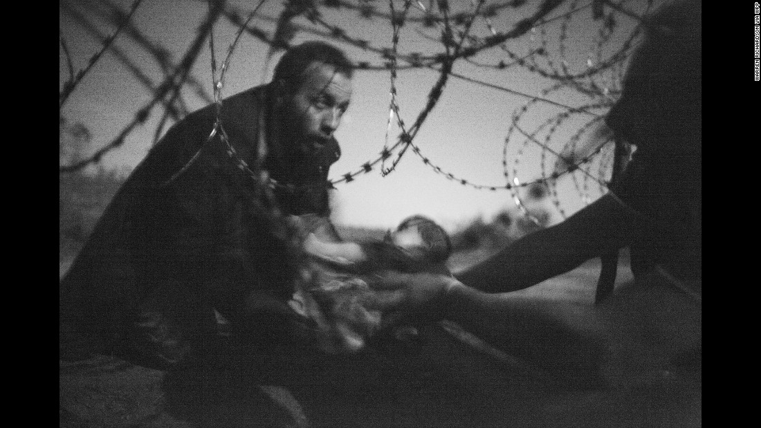 A man passes a baby through a fence at the Serbia-Hungary border on August 28. This image also won first place in the Spot News category for single photographs.
