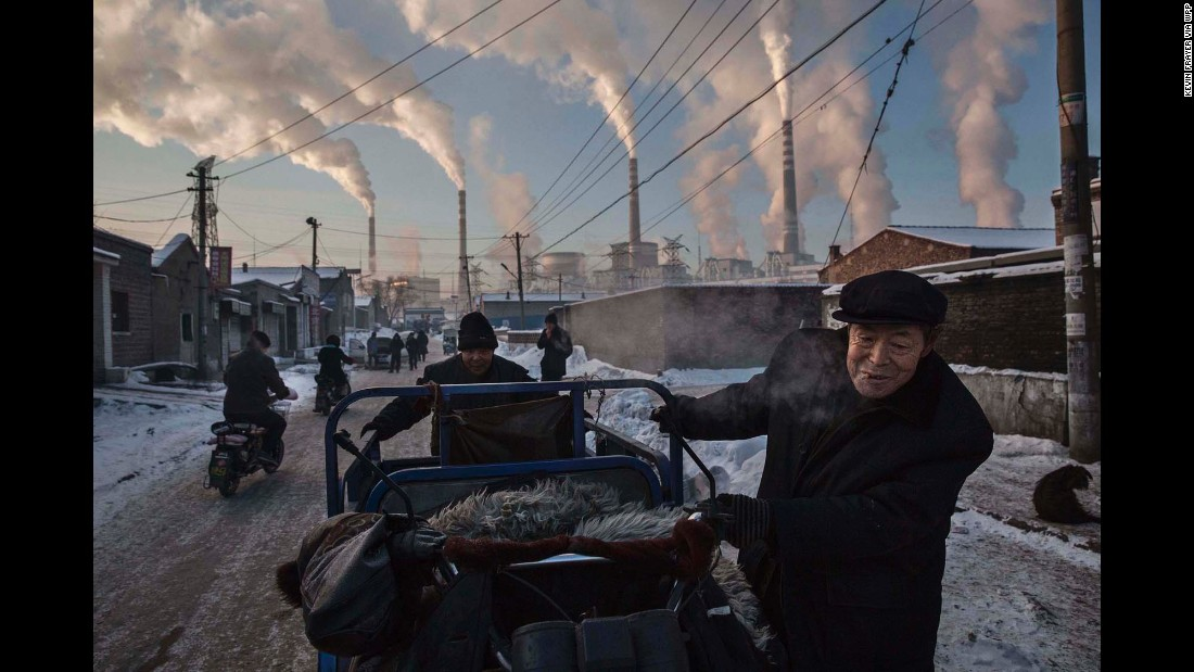 Chinese men pull a tricycle next to a coal-fired power plant in Shanxi, China, on November 26.