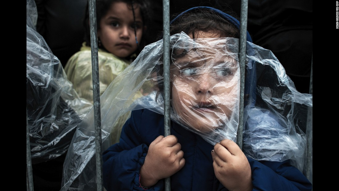 A child's face is covered with a raincoat as she waits to register at a refugee camp in Presevo, Serbia, on October 7.