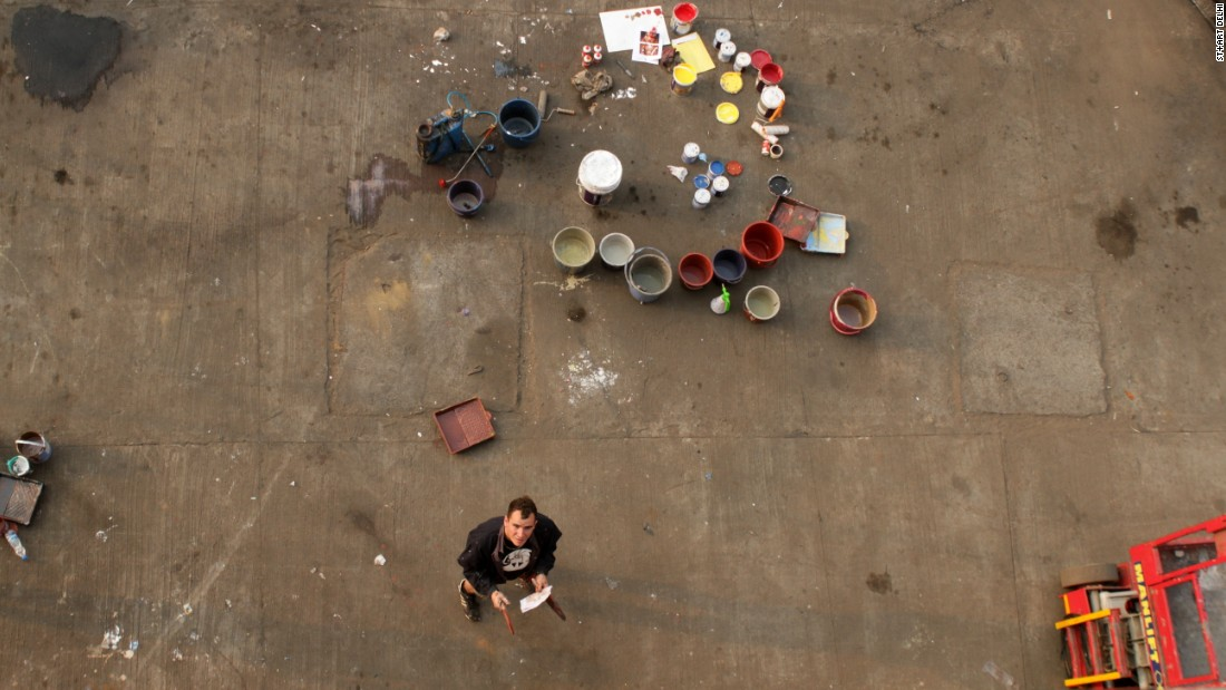 Borondo at work at the Inland Container Depot. <br />The containers deliver fruits and vegetables around India and will go back to their duties in their new painted forms, bringing art to the rest of the subcontinent. <em>(Photograph by Shijo George)</em><br />