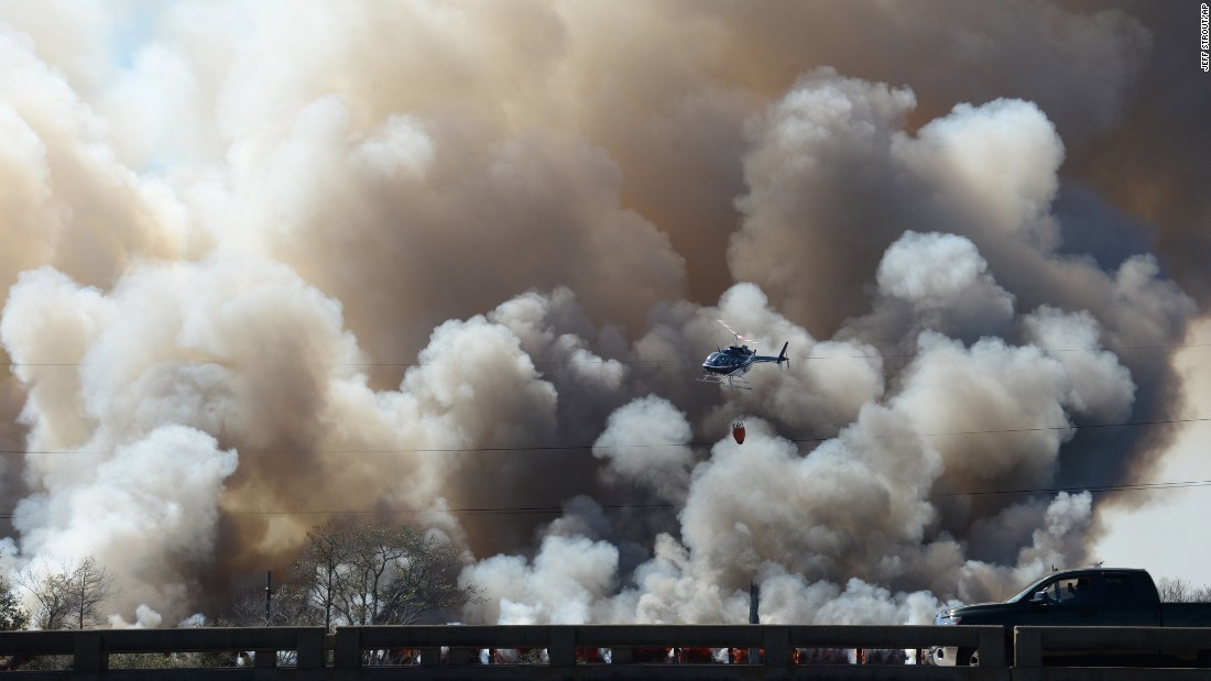 A helicopter helps fight a fire on a train trestle near the Bonnet Carre Spillway, west of New Orleans, on Saturday, February 13. The cause of the fire is under investigation.