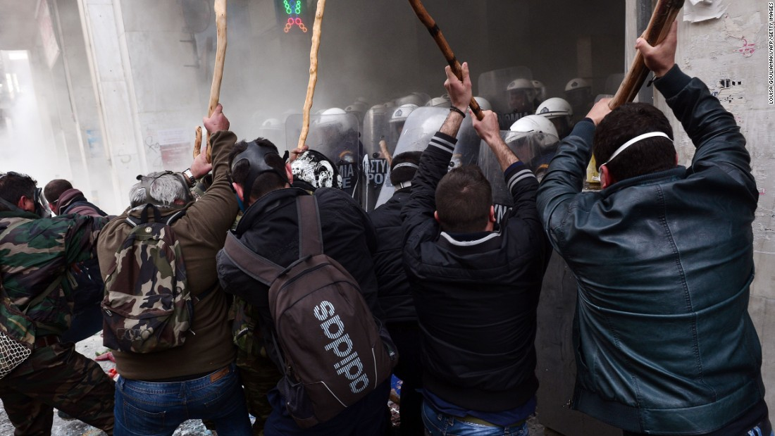 Farmers clash with police officers blocking the entrance of the Agriculture Ministry in Athens, Greece, during a demonstration against pension reform on Friday, February 12.