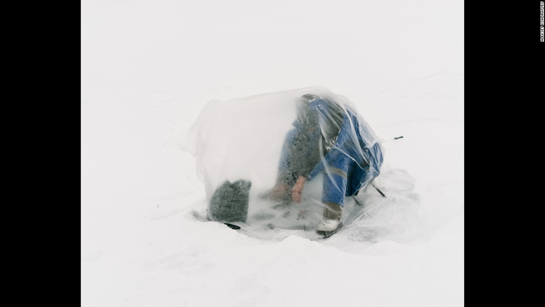 A fisherman covers himself with a plastic bag to shield himself from the wind and cold in Astana, Kazakhstan.