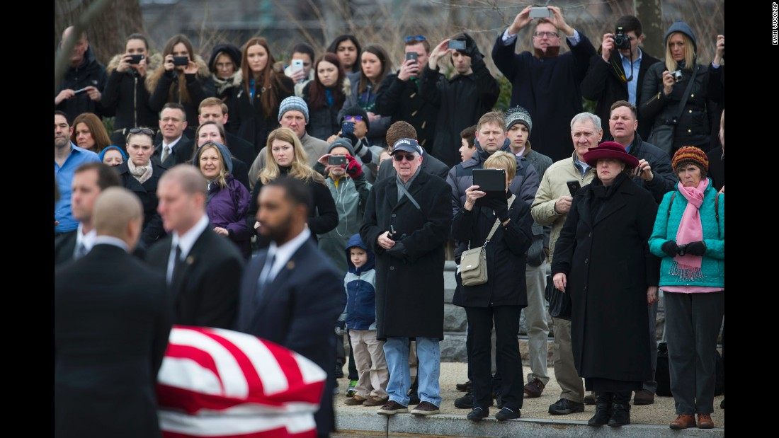 People watch as Scalia's casket is carried toward the Supreme Court building.