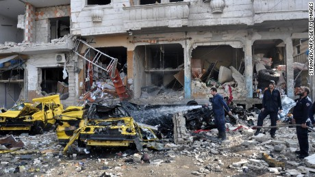 Firefighters spray water on a burning car at the bombing site in Homs.