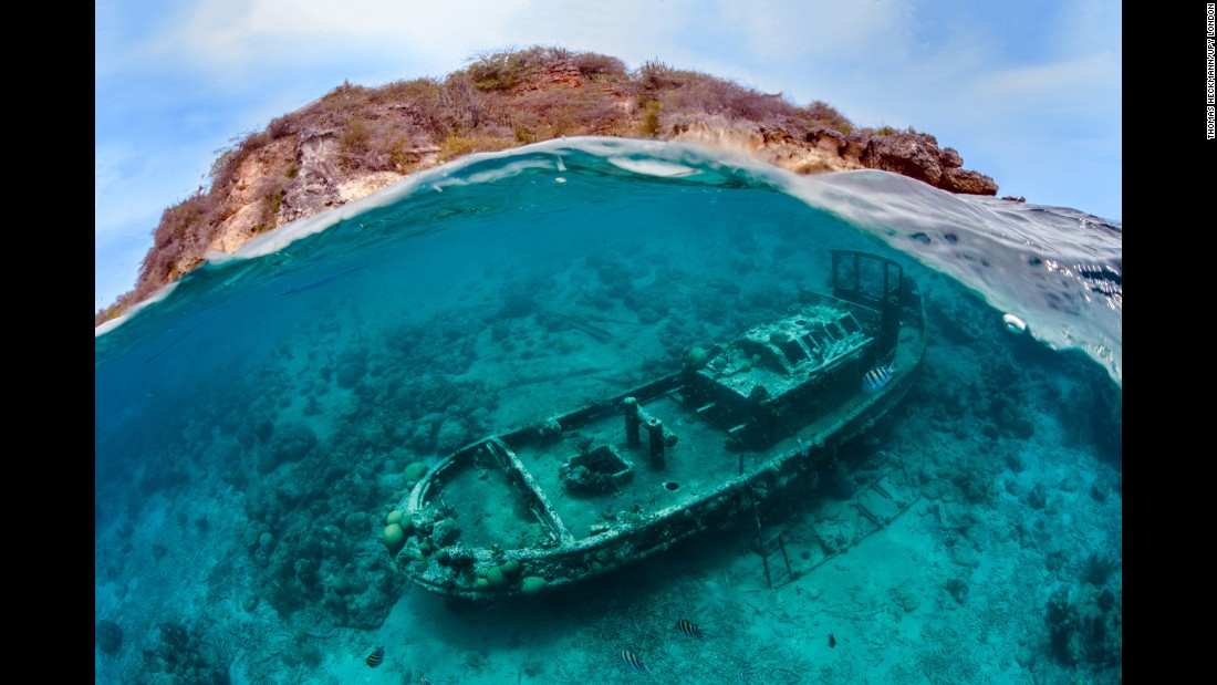 "Thomas Heckmann captured ""A Family Affair,"" which shows a shipwreck with the island of Curacao in the background. He got this shot while swimming with his young daughter, Maja."