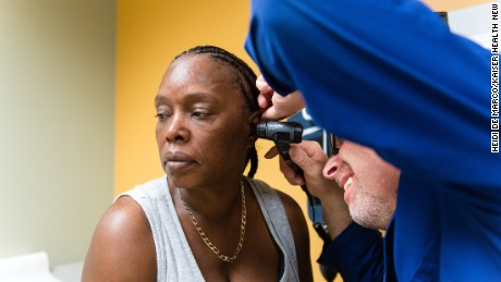 Tracy Young, 50, gets her ears checked by Brian Schlesinger, a physician's assistant, during her physical exam.