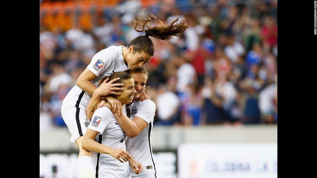 U.S. soccer players Kelley O'Hara, top, and Lindsey Horan, right, congratulate Tobin Heath after Heath scored a second-half goal against Canada on Sunday, February 21. The United States defeated Canada 2-0 to win the final of the CONCACAF tournament in Houston.