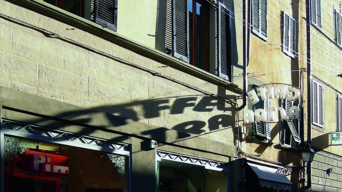 Afternoon sun casting shadows from the Caffè Astra sign in Pisa.