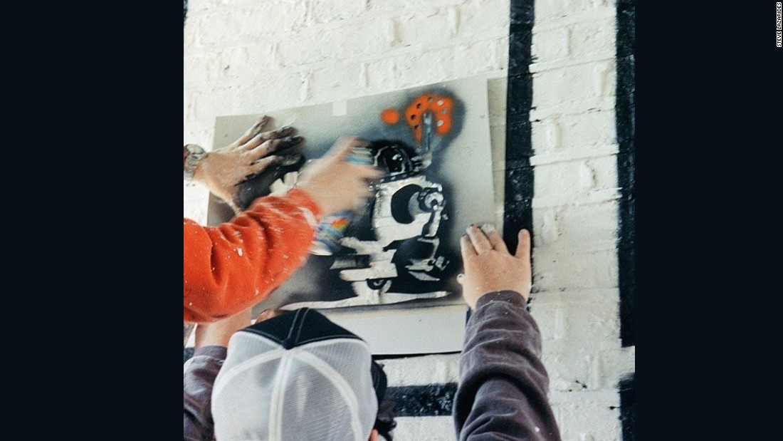 """This is an early picture of Banksy at work, from many years ago, when he was first starting out. Here he was adding to an unofficial street art exhibition in Rivington Street in Shoreditch, while I documented the whole thing with my camera.""<br />"