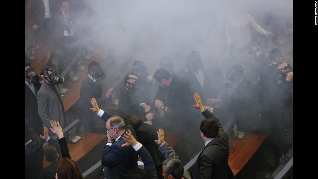 Lawmakers of Kosovo's ruling parties vote in the foreground as opposition lawmakers throw tear gas during a parliamentary session in Pristina, Kosovo, on Friday, February 19. The opposition was protesting agreements the government had made with Serbia.
