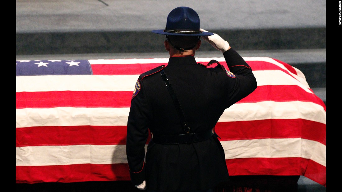 A member of the Mississippi Highway Patrol Honor Guard salutes the casket of James Lee Tartt prior to his funeral service in Grenada, Mississippi, on Tuesday, February 23. Tartt, an agent with the Mississippi Bureau of Narcotics, was fatally shot in a standoff with a suspect.