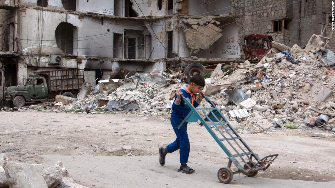 A boy walks a hand truck through a heavily damaged area in Aleppo.