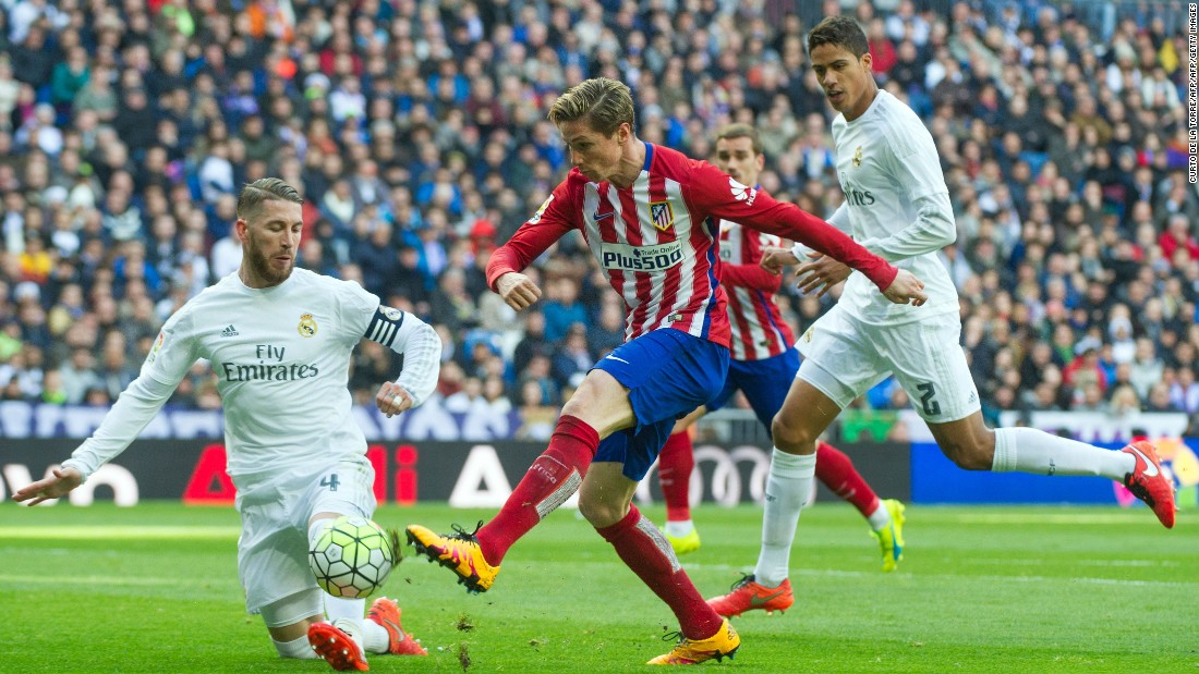 Real Madrid's defender Sergio Ramos (L) vies with Atletico Madrid forward Fernando Torres.
