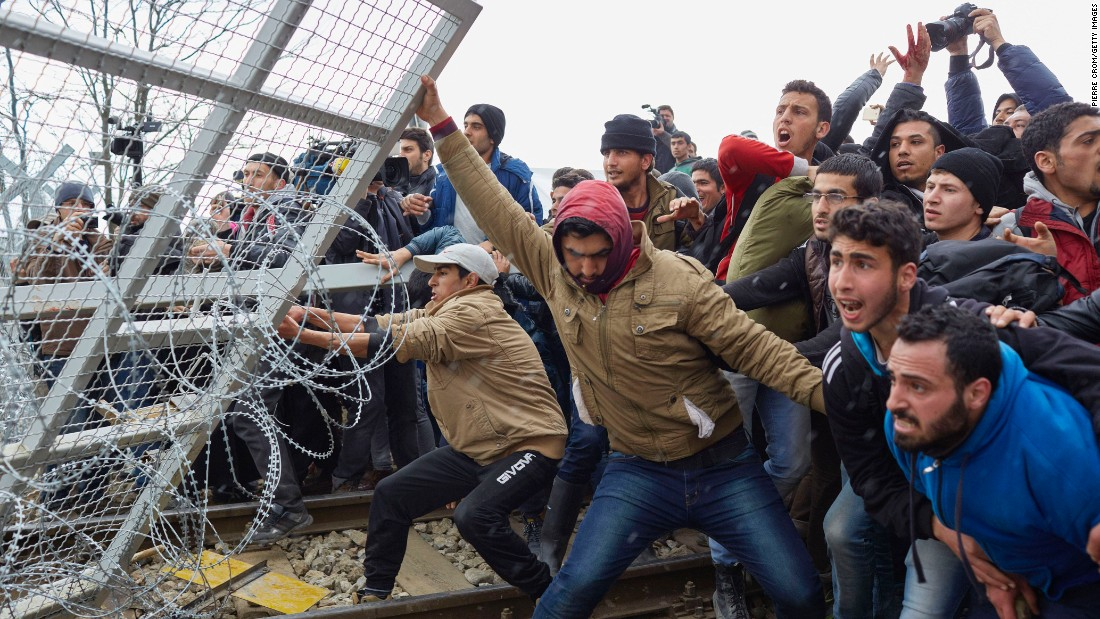 Refugees break through a barbed-wire fence on the Greece-Macedonia border in February 2016, as tensions boiled over regarding new travel restrictions into Europe.