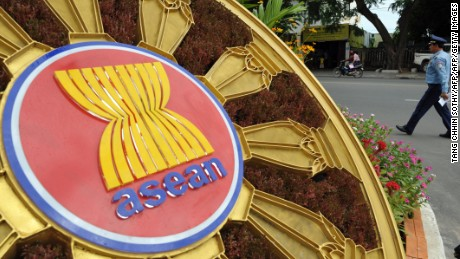 A Cambodian police officer (R) walks past the ASEAN logo in front of the Peace Palace during the 45th Association of Southeast Asian Nations (ASEAN) Foreign Ministers' Meeting (AMM) in Phnom Penh on July 8, 2012.  Efforts to ease tensions in the South China Sea will dominate this week's Asian security dialogue in Cambodia, analysts say, while the US will be at pains to stress it seeks cooperation, not rivalry, with China.      AFP PHOTO / TANG CHHIN SOTHY        (Photo credit should read TANG CHHIN SOTHY/AFP/GettyImages)