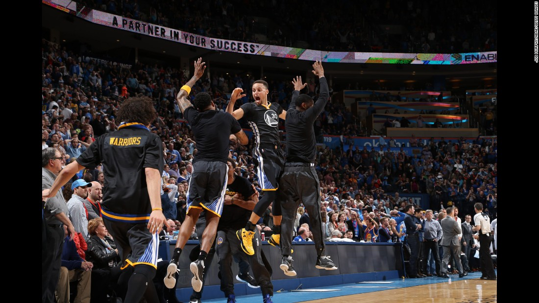 Golden State guard Stephen Curry (No. 30) celebrates with teammates after he hit a long 3-pointer to win in Oklahoma City on Saturday, February 27. Curry made 12 3-pointers in the game and finished with 46 points.