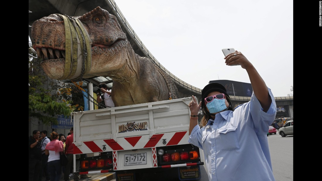 A man takes a selfie as a dinosaur model is transported in Bangkok, Thailand, on Monday, February 29.