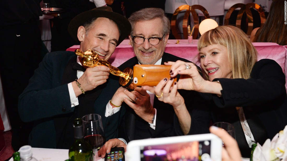 "Mark Rylance holds up the Oscar he won for best supporting actor as he sits with ""Bridge of Spies"" director Steven Spielberg and Spielberg's wife, Kate Capshaw, at an Oscars after-party on Sunday, February 28."