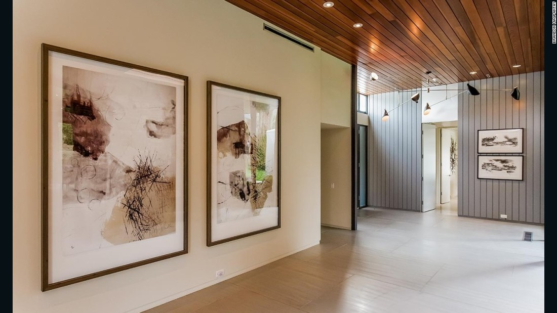 The property's interiors feature floor-to-ceiling glass walls, wooden ceilings and stone walls.