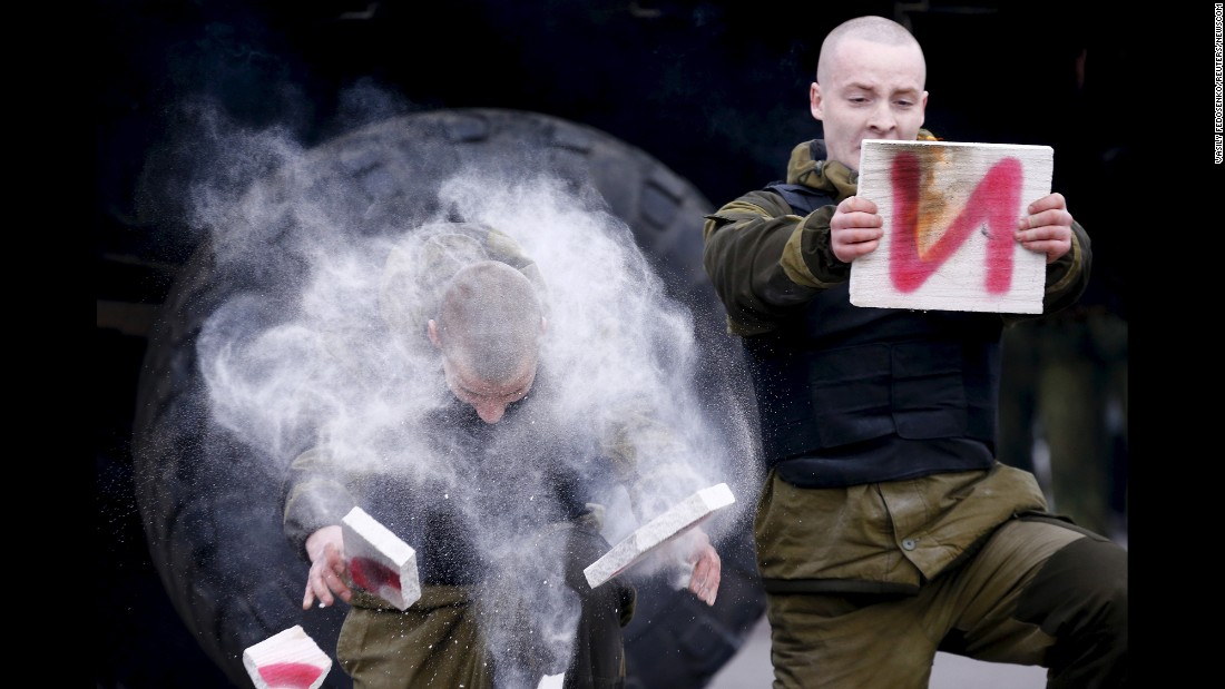 Men break wooden boards during Maslenitsa celebrations in Minsk, Belarus, on Sunday, February 28. The men serve in the special forces unit of the Belarussian Interior Ministry. Maslenitsa, a holiday marking the end of winter, is traditionally celebrated with pancake eating and feats of strength.