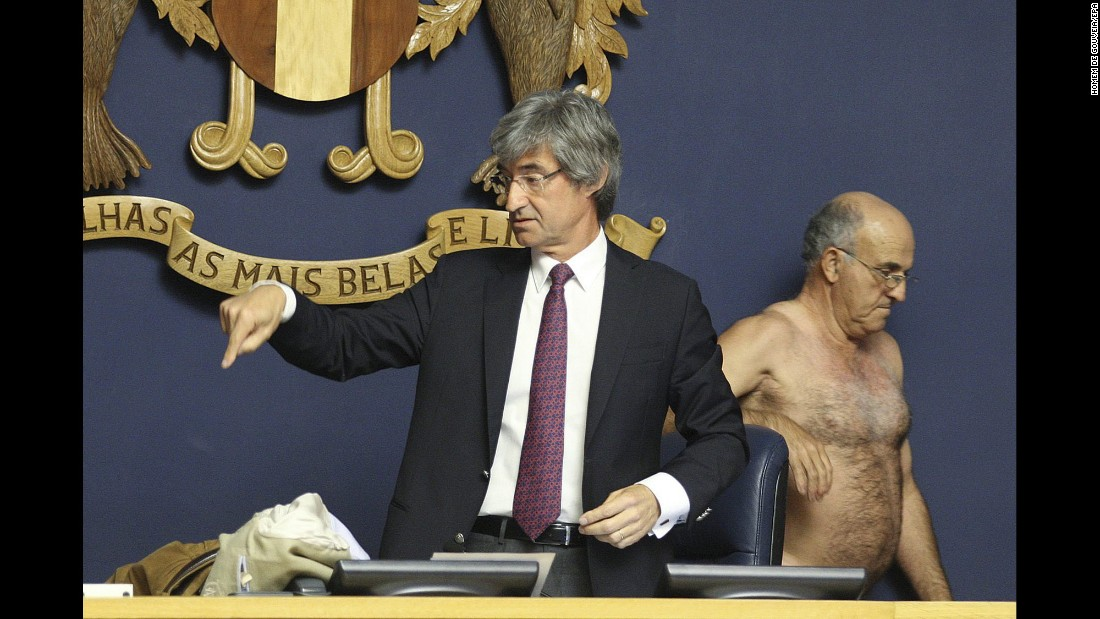 Jose Tranquada Gomes, president of the Madeira Island Legislative Assembly, points to clothes left on his desk by Jose Manuel Coelho, a Portuguese Labor Party deputy, on Thursday, March 3. Coelho undressed himself to protest a court's decision to cut part of his salary.
