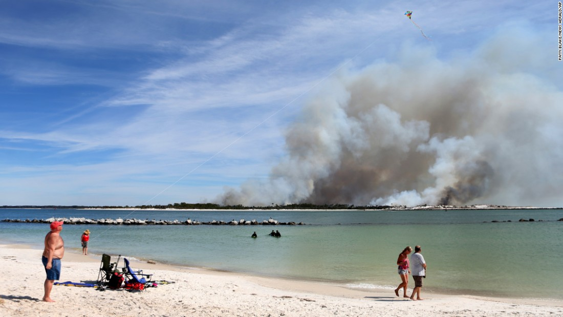 People walk on a beach in Panama City, Florida, as a controlled fire releases smoke over Shell Island on Wednesday, March 2.