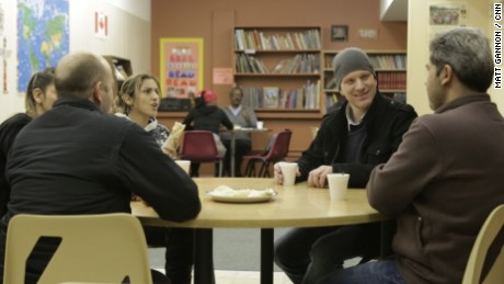 Ryan Dueck, second from right, stops in at a language center for a coffee and conversation with members of the Syrian family his church sponsored.