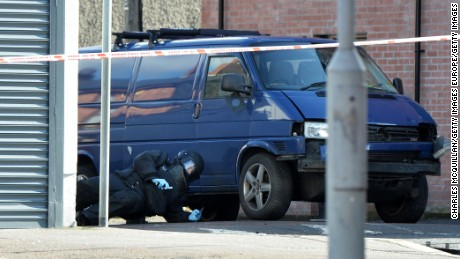 A bomb disposal unit officer checks a van damaged in a car bomb attack Friday in Belfast.