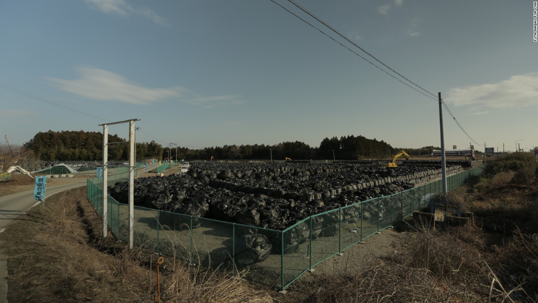 A mountain of black bags filled with contaminated soil sits piled on a roadside in Tomioka, Fukushima. A massive national project to remove topsoil and vegetation contaminated by the Fukushima nuclear disaster will produce at least 22 million square meters of radioactive waste.