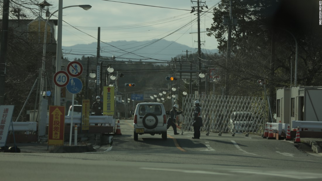 Security guards check passes within the Fukushima exclusion zone, former residents may only visit for up to 5 hours at a time.