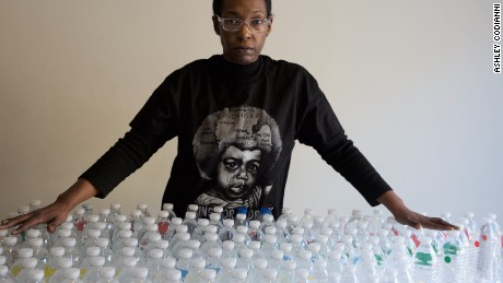 Gina Luster in her Flint, Michigan home with the total bottles of water it takes to get through a day