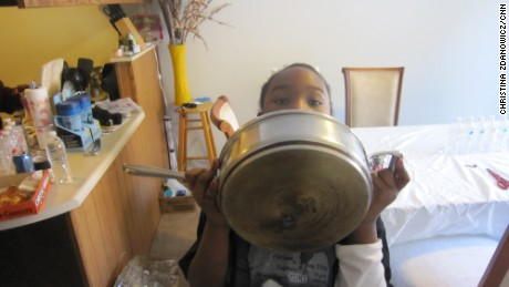Kennedy Luster, 7, holds a pot her mother says was ruined by washing it in Flint's water.