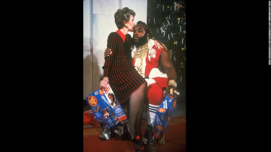 Reagan sits on the lap of Mr. T, dressed as Santa Claus, during a  White House Christmas decoration tour in 1983.