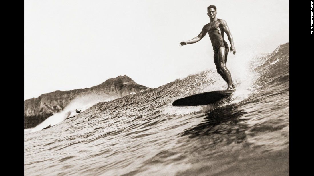 This surfer was photographed by Tom Blake around 1932. Blake designed and built the first camera water housings to take close-up surfing photographs. He would wade out and stand on the shallow reef at Waikiki or take a canoe out to deeper water. A surfer himself, Blake had a natural eye for framing the wave and the rider in a way that caught the peak of action.